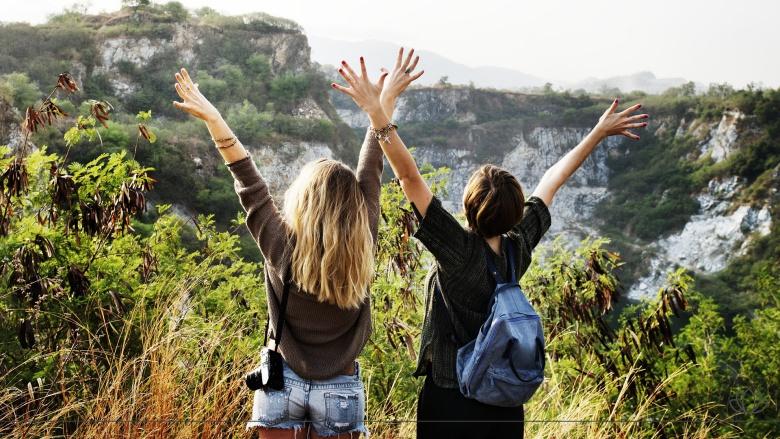 山の上で喜んでいる女性2人の画像